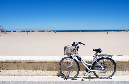 a bicycle parked in the seafront of the popular La Malvarrosa beach, in Valencia, Spain