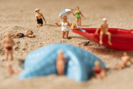 bather: some different miniature people wearing swimsuit relaxing next to a blue plastic starfish and a red toy shovel on the sand of the beach