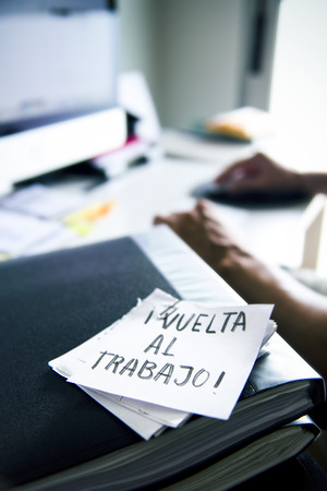 closeup of a man sitting at his office desk and a note in the foreground with the text vuelta al trabajo, back to work written in spanish