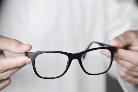 closeup of a young optician man bringing a pair of eyeglasses to the observer Stock Photo