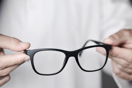 gros plan d & # 39 ; un jeune homme opticien ouvre une paire de lunettes à l & # 39 ; observateur
