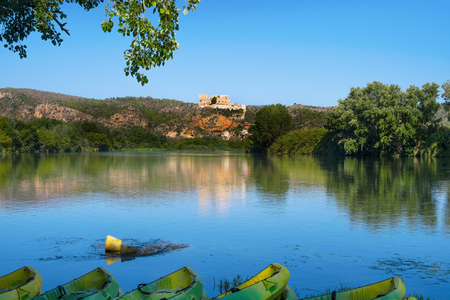 some kayaks at the Ebro River passing through Miravet, Spain, highlighting its Templar castle in the top of the hill