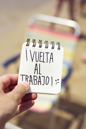 closeup of a young man in the beach showing a spiral notepad with the text vuelta al trabajo, back to work in Spanish, in front of a deck chair in the seashore