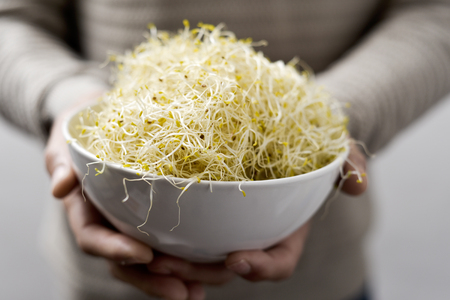 closeup of a young caucasian man with a white ceramic bowl full of alfalfa sprouts Stock Photo