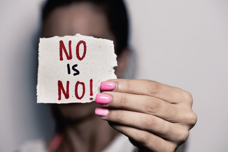 egalitarianism: closeup of a young caucasian woman with pink polished nails holding a piece of paper with the text no is no written in it, in front of her face Stock Photo