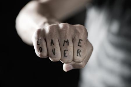 close-up van de hand van een jonge blanke man met het tekstspel geschreven met een tijdelijke inkt in zijn knokkels, met een dramatisch effect