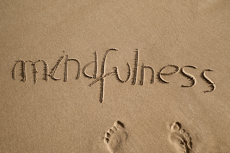 high-angle shot of the word mindfulness written in the sand of a beach and a pair of human footprints Archivio Fotografico