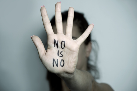 egalitarianism: closeup of the hand of a young caucasian woman in front of her face with the text no is no written in her palm