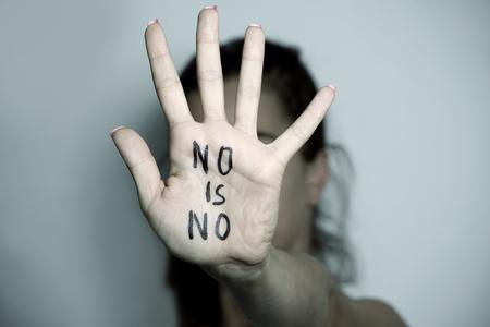 Portarretrato de la mano de una joven caucásica mujer delante de su cara con el texto no es no escrito en su mano Foto de archivo - 84934995
