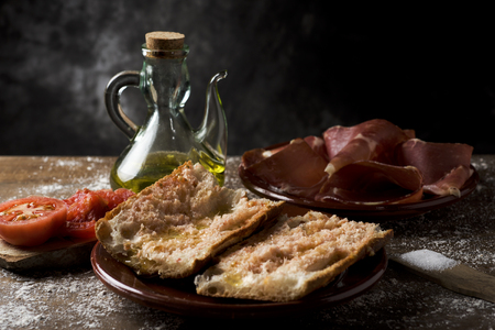 closeup of a plate with typical catalan pa amb tomaquet, bread with tomato dressed with olive oil, a plate with some slices of serrano ham and a cruet with olive oil, on a rustic wooden table