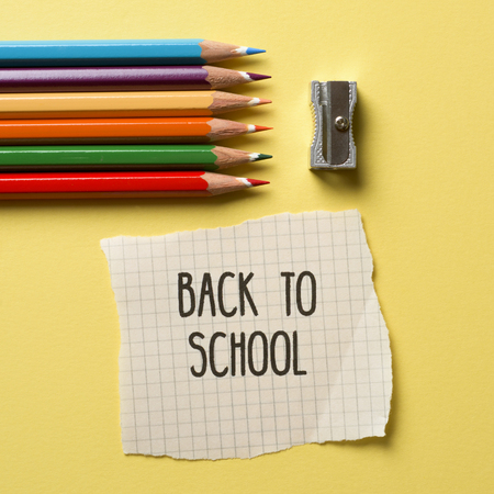 high-angle shot of some pencil crayon of different colors, a metallic sharpener and a note with the text back to school on a yellow background