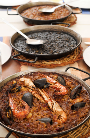 closeup of some paelleras, the paella pan, with a typical spanish seafood paella, an arroz negro or black paella, made with squid ink, and a fideua or noodle paella on a table set for lunch