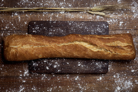 high-angle shot of a loaf of pa de vidre or pa de coca, a bread typical of Catalonia, Spain, on a rustic wooden table Banque d'images