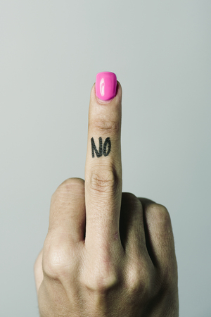 closeup of the hand of a young caucasian woman giving the middle finger with the word no handwritten in it, against an off-white background