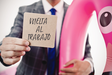 closeup of a young caucasian businessman wearing a swim ring in the shape of a pink flamingo showing a brown signboard with the text vuelta al trabajo, back to work written in spanish Stock Photo