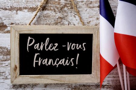 una pizarra de madera con la pregunta parlez-vous francais? ¿Habla usted francés? escrito en francés, y algunas banderas de Francia contra un fondo de madera rústica