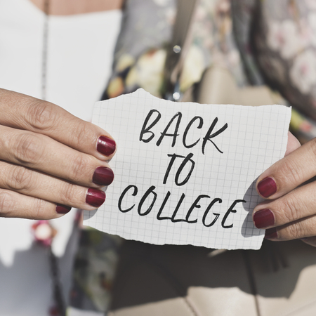 closeup of a caucasian student outdoors, with her nails painted red, showing a note with the text back to college written in it