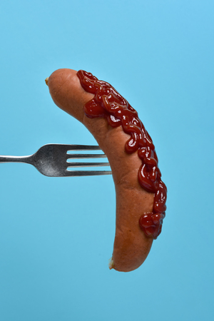 closeup of a hot dog topped with ketchup in a fork against a bright blue background