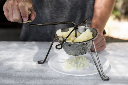 closeup of a young caucasian man mashing boiled potatoes with an old grinder