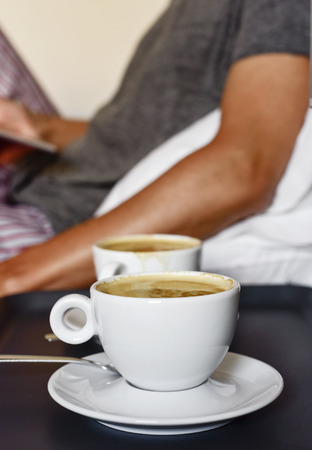 closeup of a pair of cups of coffee on a nightstand and a young caucasian man in pajamas in the background sitting in bed while is using a tablet or an e-reader