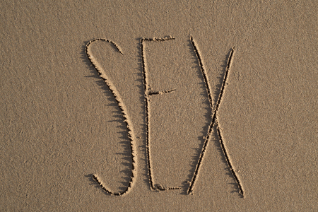 high-angle shot of the word sex written on the sand of a beach Banque d'images