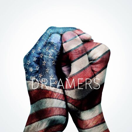 closeup of the hands of a man put together patterned as the flag of the United States and the text dreamers, for the beneficiaries of the Dream Act, on an off-white background