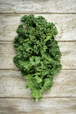 closeup of a kale leaf on a rustic wooden table