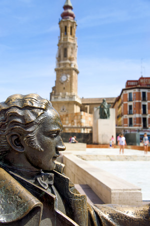 a view of the Plaza del Pilar square in Zaragoza, Spain, with the monument to Goya in the foreground and the Cathedral of the Savior or La Seo in the background