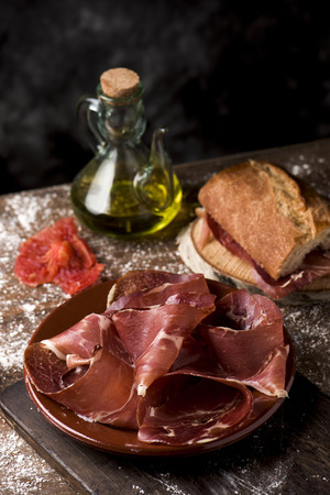 a plate with some slices of serrano ham on a rustic wooden table, next to a cruet with olive oil and a sandwich of typical catalan pa amb tomaquet, bread with tomato, stuffed with serrano ham Banque d'images