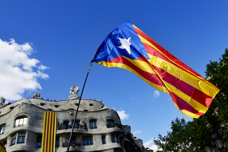 BARCELONA, SPAIN - SEPTEMBER 11, 2017: An estelada, the Catalan independentist flag in Barcelona, Spain, during a rally for the independence of Catalonia, and the famous Casa Mila in the background