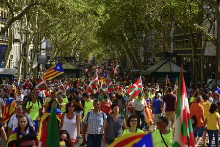 BARCELONA, SPAIN - SEPTEMBER 11, 2017: People in Las Ramblas going to partake in a rally in support for the independence of Catalonia, with Catalan independentist flags and flags of the Basque Country