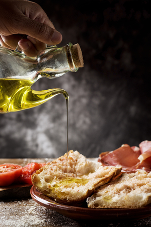 closeup of a man dressing with olive oil some slices of typical catalan pa amb tomaquet, bread with tomato, placed on a plate on a rustic wooden table next to a plate with some slices of serrano ham
