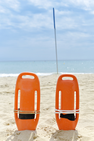 closeup of some colorful rescue buoys in the sand of a quiet beach in the Mediterranean sea Stock Photo