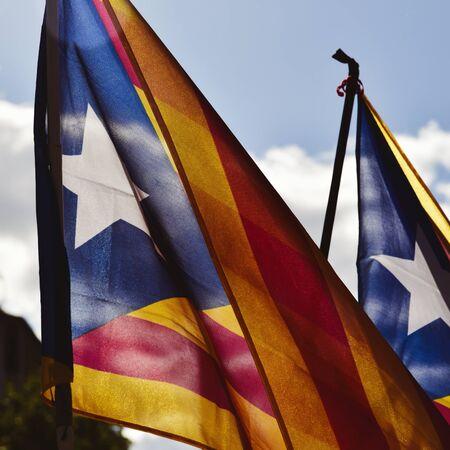 algunos estelada, la bandera catalanista pro-independencia, contra el cielo, con un efecto retro Foto de archivo