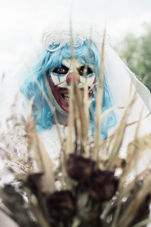closeup of a scary evil clown wearing a dirty and ragged bride dress holding a bridal bouquet with wilt flowers in front of the observer