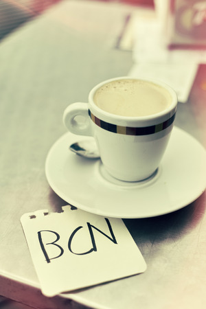 closeup of a cup of coffee and a note with the word BCN, for Barcelona, written in it, on a table in the terrace of a cafe in Barcelona, Spain, with a retro effect