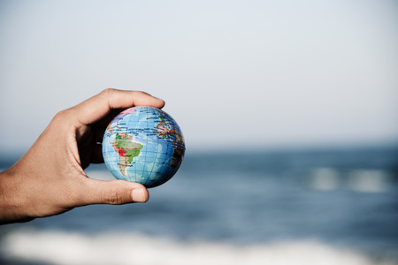 closeup of a young caucasian man with a world globe in his hand in front of the sea, with a blank space on the right