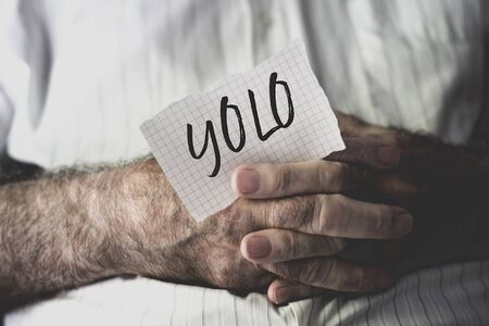 closeup of an old caucasian man with a note in his hands with the word yolo, for you only live once, written in it Banque d'images