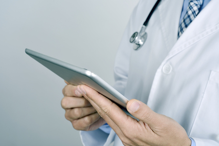 closeup of a young caucasian doctor man wearing a white coat and a stethoscope using a tablet computer