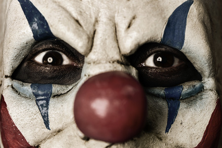 closeup of a scary evil clown with a disturbing look in his eyes Stock Photo - 87017639