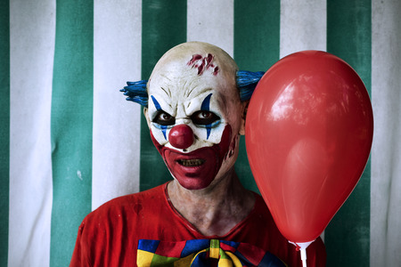 closeup of a scary evil clown wearing a dirty costume and holding a red balloon, with the circus tent in the background Stock Photo