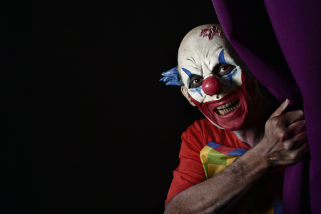 closeup of a scary evil clown peering out from a purple stage curtain, with a blank black space on the left Stock Photo