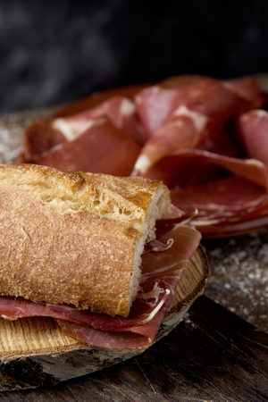 closeup of a typical spanish bocadillo de jamon, a serrano ham sandwich, on a rustic wooden table, next to a plate with some slices of serrano ham