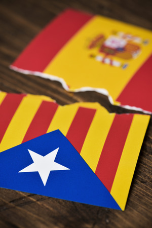 the Estelada, the Catalan pro-independence flag and the flag of Spain, broken on a rusitc wooden surface