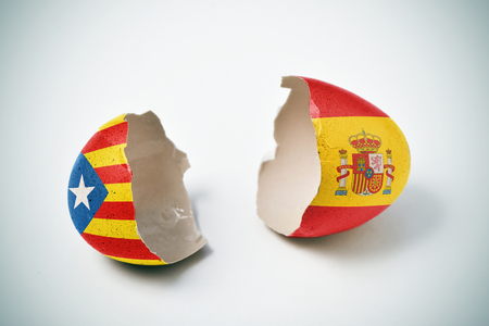 the two halves of a cracked eggshell, one patterned with the Estelada, the Catalan pro-independence flag and the other one patterned with the flag of Spain Stock fotó - 87653898