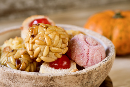 closeup of a rustic bowl with some panellets, typical confection eaten in All Saints Day in Catalonia, Spain, on a wooden table, and a pumpkin in the background