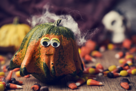 a pumpkin with funny eyes surrounded by halloween candies on a rustic wooden table and a skull in the background Stock Photo