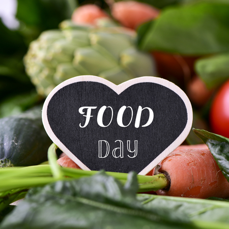 closeup of a heart-shaped chalkboard with the text food day placed on a pile of some different raw vegetables, such as tomatoes, spinach, carrots or artichokes Stock Photo