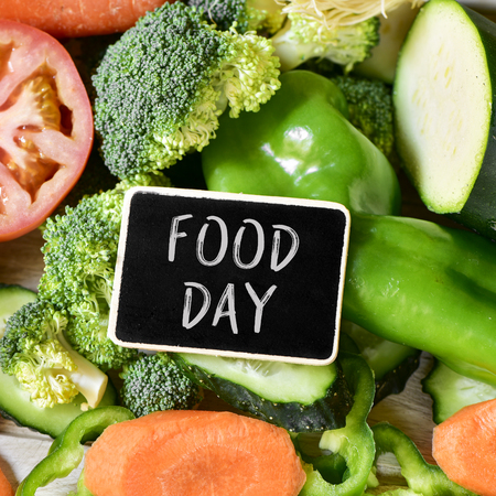 closeup of a heart-shaped chalkboard with the text food day placed on a pile of some different raw vegetables, such as tomatoes, carrots, peppers, or broccoli