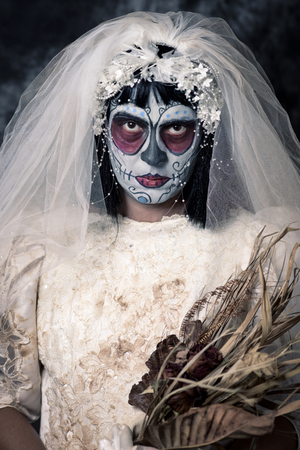 terrifying: portrait of a bride with a mexican calaveras makeup, wearing diadem and veil, holding a bridal bouquet of wilted flowers Stock Photo